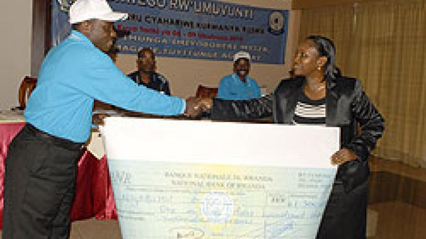 The Mayor of Nyabihu, Jean Damaciene Ndajimana receiving cheque of Rwf1.3 million after his district emerged the best (Courtsey Photo).