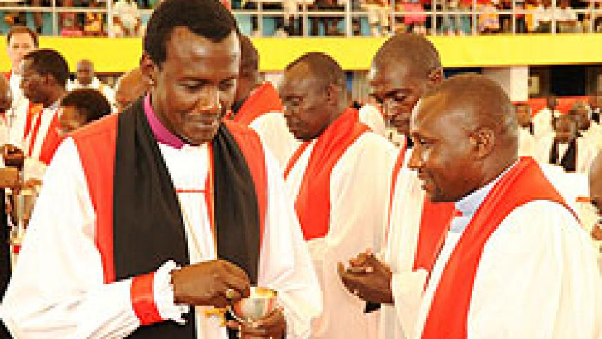 Louis Muvunyi the new consecrated Bishop of Kigali giving the Holy communion to fellow clergymen during the consecration (Photo T.Kisambira)