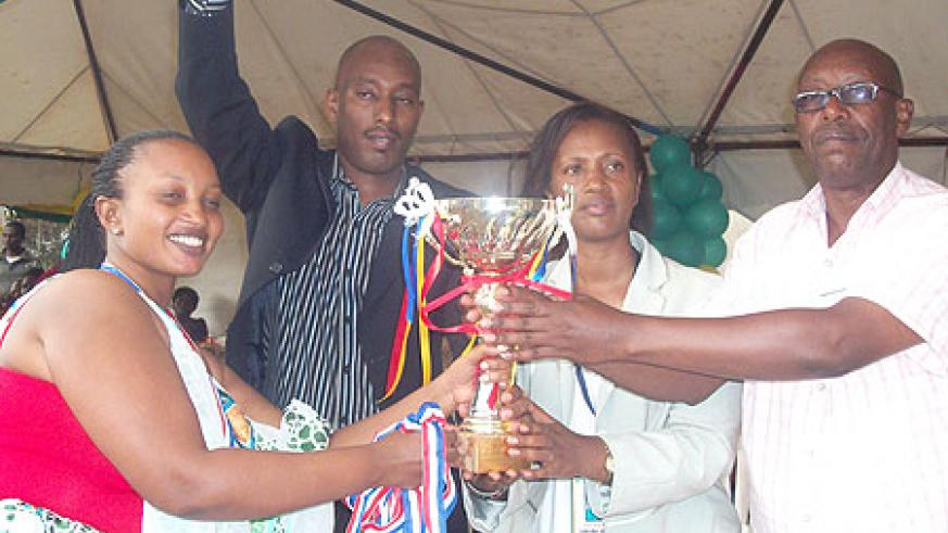 Jeanne D'arc Gakuba, the Kigali City Mayor in charge of Social Affairs (C), Rwanda's First Secretary to Uganda (in a black suit), Jacqueline Umulisa  and another guest pose with the trophy.