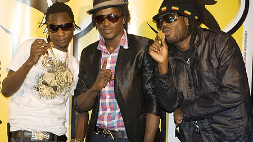 Davis Ntare (c) poses with renowned Ugandan artists Coco Finger (L) and Bebe Cool(R).