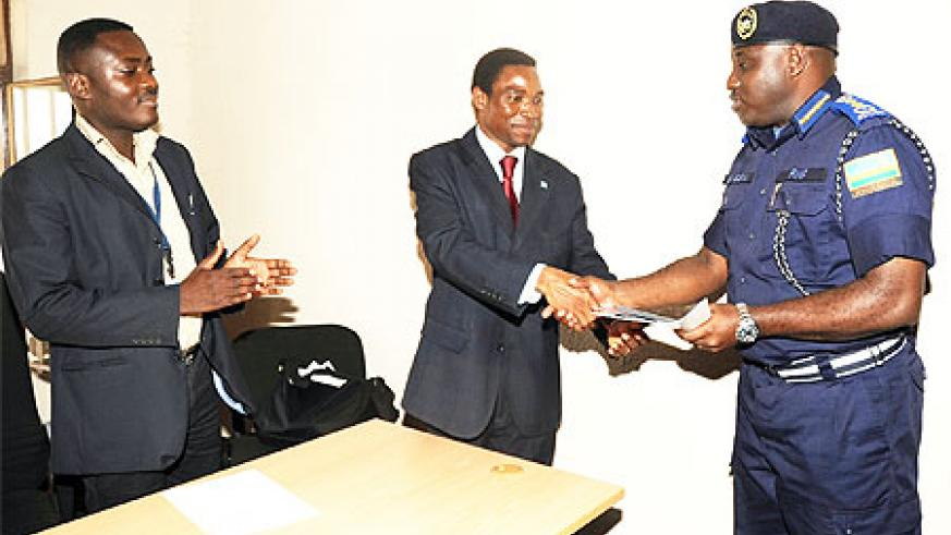 The Commissioner General of Police Emmanuel Gasana receives the software from Rodger Glokpor from the UN office for Disarmament Affairs.(Photo J Mbanda)
