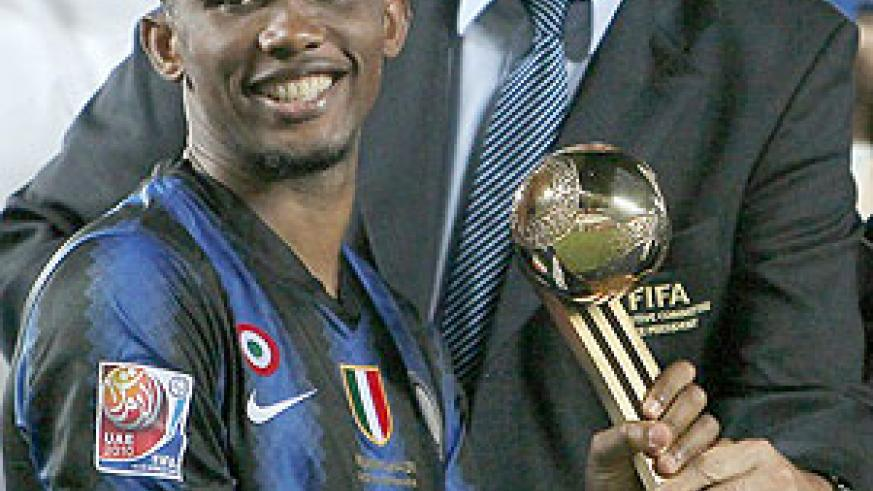 Inter Milan's Cameroonian striker Samuel Eto'o (L) receives the golden ball trophy from UEFA president Michel Platini after his team won the 2010 FIFA Club World Cup. (Net photo)