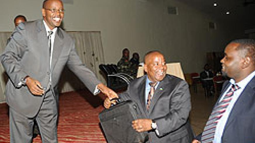 Local Government Minister James Musoni (L) hands over a laptop to the Governor of Northern Province Aime Bosenibamwe. (Photo / J. Mbanda)
