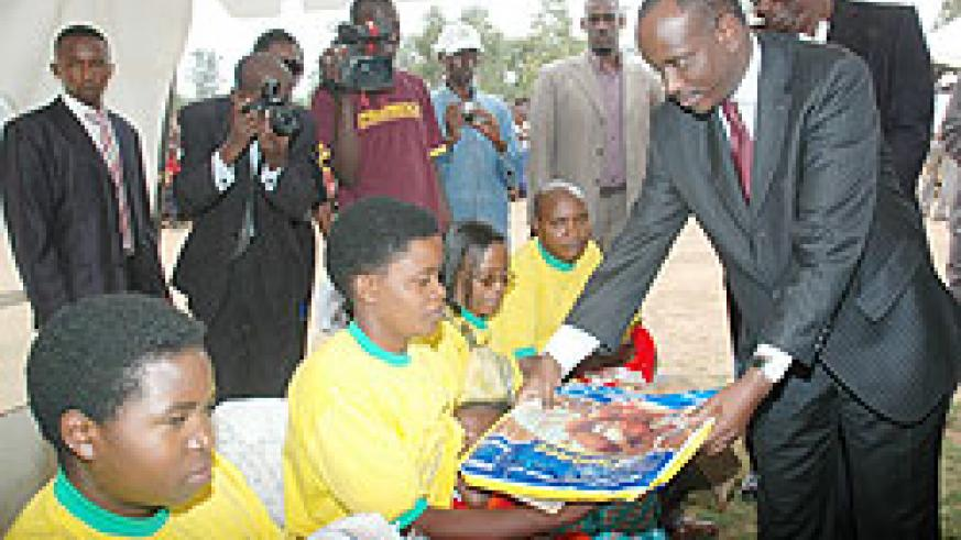 Dr. Richard Sezibera gives a Mosquito net to a Mother in Gashora at the launch of the Immunisation Program recently. (File photo)