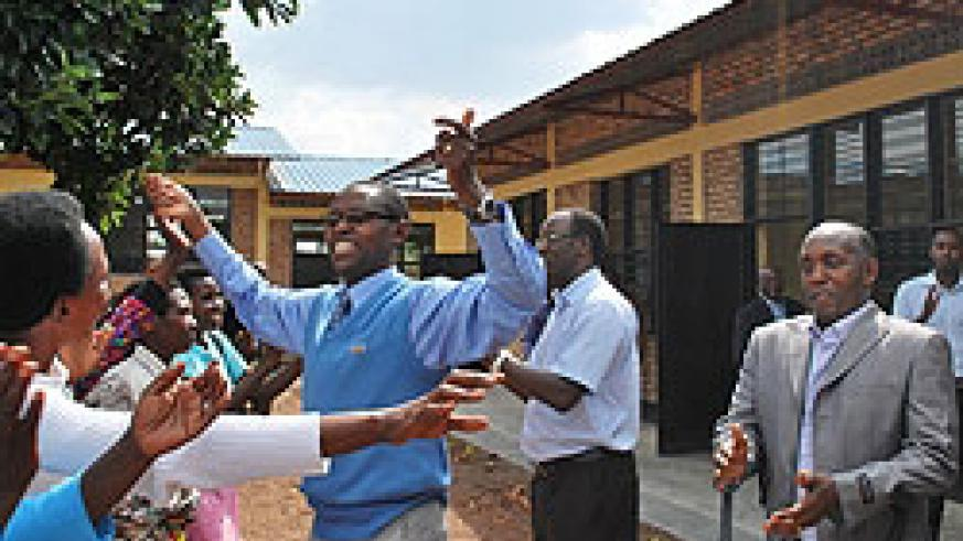 State Minister for Primary  and Secondary Education, Dr Mathias Harebamungu, joins  residents in celebrating construction of the 90 classrooms in Kamonyi district. (File Photo)