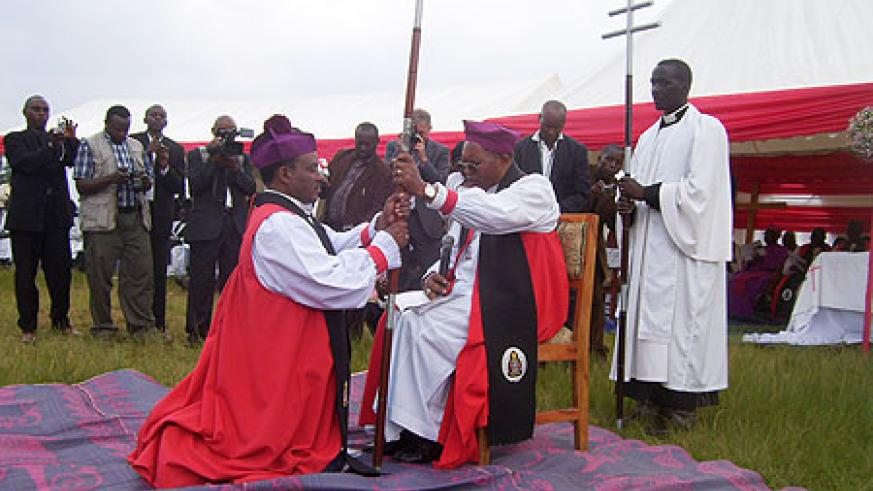 Archbishop Kolini (R) hands over the Bishop's Mass to Bishop Emmanuel Ngendahayo during the inauguration ceremony. (Photo by A.Gahene)