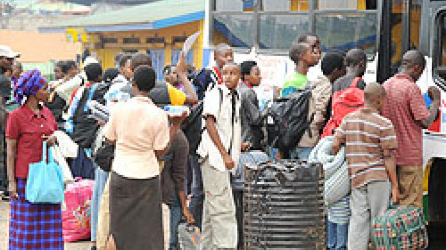 BACK TO SCHOOL; Students queue up to board a bus to school. Transport  becomes a problem on first days of school (Photo T. Kisambira)