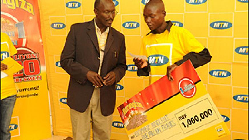 Andrew Rugege, MTN's COO after handing over a cheque to one of the winners, Innocent Bizimana,  recently (File Photo)