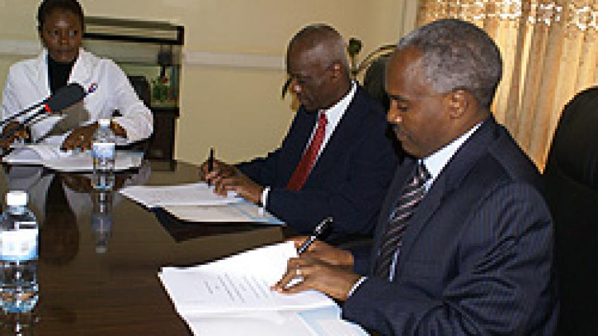 Ministers Charles Murigande (right) and  Evans Lescouflair signing the MoU yesterday (Courtesy photo)