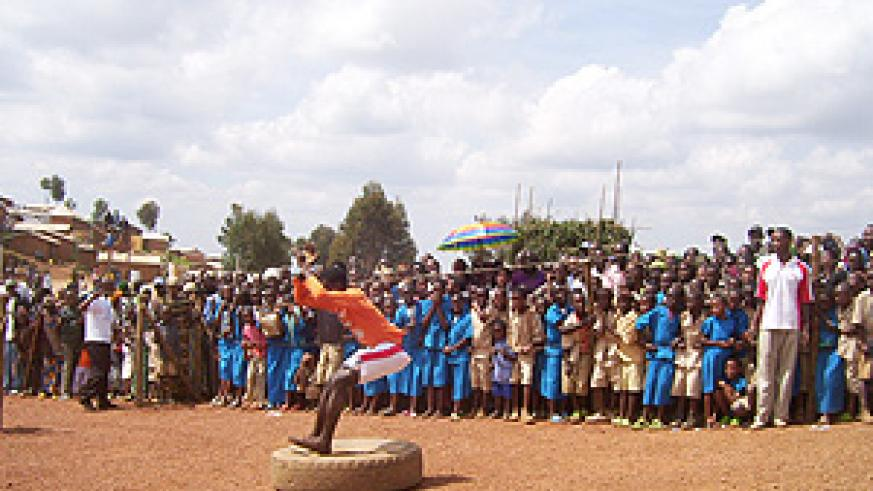 Children watch acrobats during celebrations to mark World Refugee Day at Gihembe Refugee camp in 2007. (File photo)