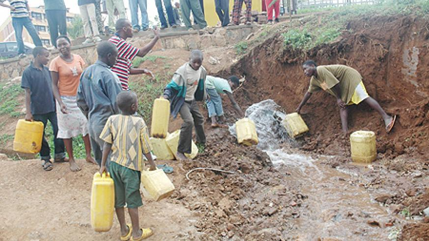 Kigali residents taking advantage of a broken pipe to get water. Shortage has been blamed on heavy rains
