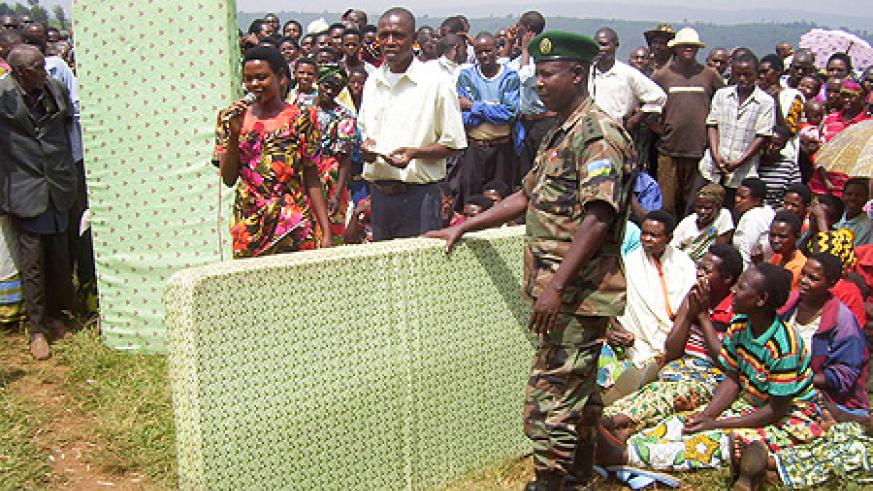 An RDF officer hands over mattresses to  residents during the Nyakatsi eradication drive in Giti Sector. Photo  A. Gahene