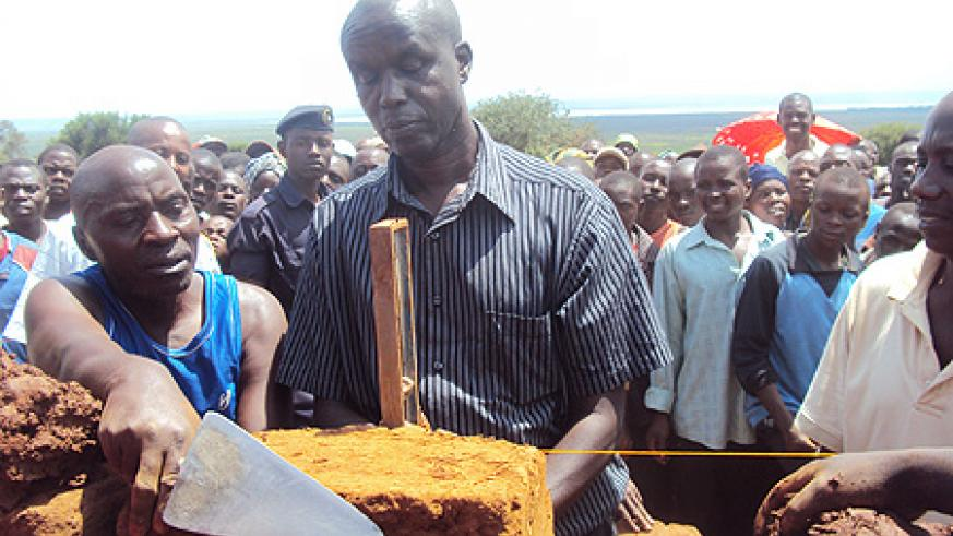Governor Kabaija engages Rweru residents in house construction. (Photo: S. Rwembeho)