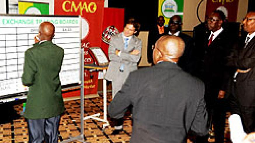 Celestin Rwabukumba of RSE conducting trading as Prime Minister Bernard Makuza and the Minister of Finance and Economic Planning, John Rwangombwa look on (PhotoT. Kisambira)