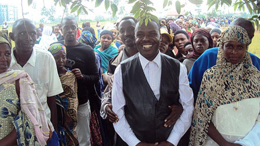 One of the local leaders re-elected all smiles at hundrends queu behind him in support.(Photo by S. Rwembeho).