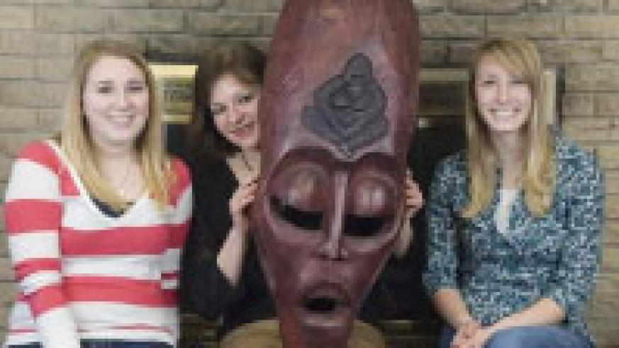 Simpson student Anna Ronnebaum, Professor Virginia Croskery and student Kayla Ferguson pose with a mask made by a Rwandan artisan. The three are part of a Simpson College group planning to travel to Rwanda in May. The mask was made for Simpson College dur