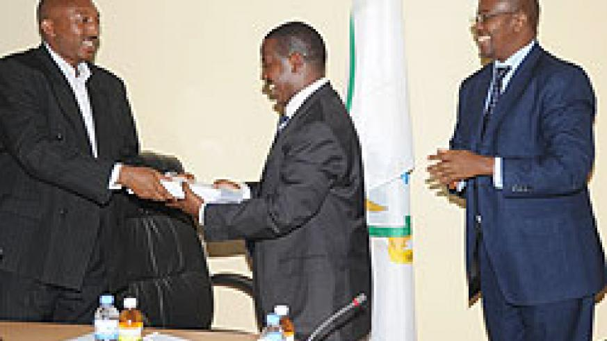 Out going Parmanent Secretary Eugene Barikana (L) hands over to the new PS Cyril Turatsinze as Local Government Minister James Musoni looks on. (Photo J Mbanda)