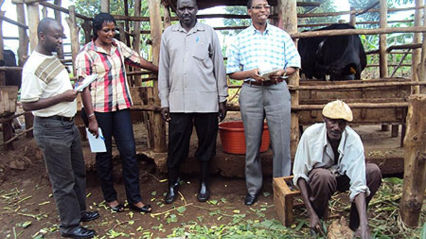 Etienne Kabera (C) a successful farmer talking to Send A Cow officials who visited his farm recently. (Photo S. Rwembeho).