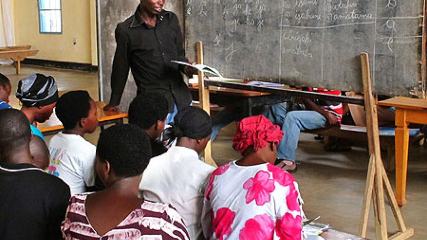 Adults taking part in a literacy class  in Kicukiro District, yesterday. (Photo T Kisambira)