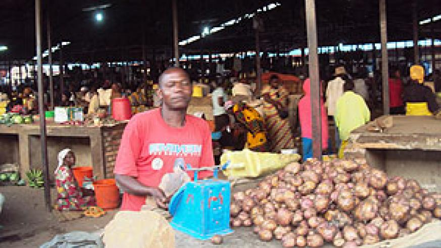 A trader using the banned weighing scale in one of the local markets. (Photo by S. Rwembeho.)