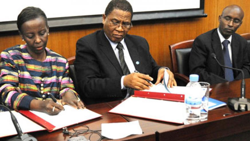 Foreign Affairs Minister, Louise Mushikiwabo (L), and COMESA Secretary General, Sindiso Ngwenya, sign the agreement as ICT Minister, Ignace Gatare, looks on. (Photo: J. Mbanda)