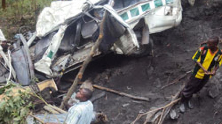 Residents at the wreckage of the taxi which was involved in the  fatal accident.Photo: B. Mukombozi.JPG