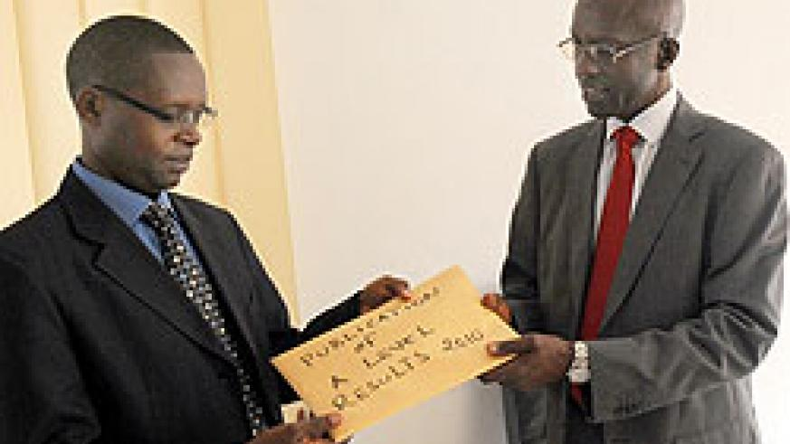 State Minister Mathias Harebamungu (L) receiving results from RNEC's John Rutayisire. Anomailes have been reported in A Level results (Photo J Mbanda)