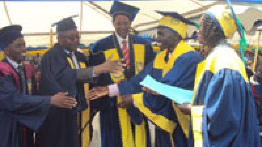 Prof Rwigamba Balinda (c) congratulating Gaspard Nzabonimpa, the best overall student ,during the ceremony yesterday (Photo A Ngarambe)