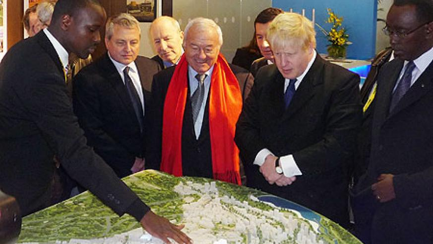 L-R-KCC's urban planner, Joshua Ashimwe explains the Kigali master plan to the Mayors of Cannes, Bernard Brochand (in red scarf) and London, Boris Johnson, as Premier Makuza looks on. (courtesy photo)