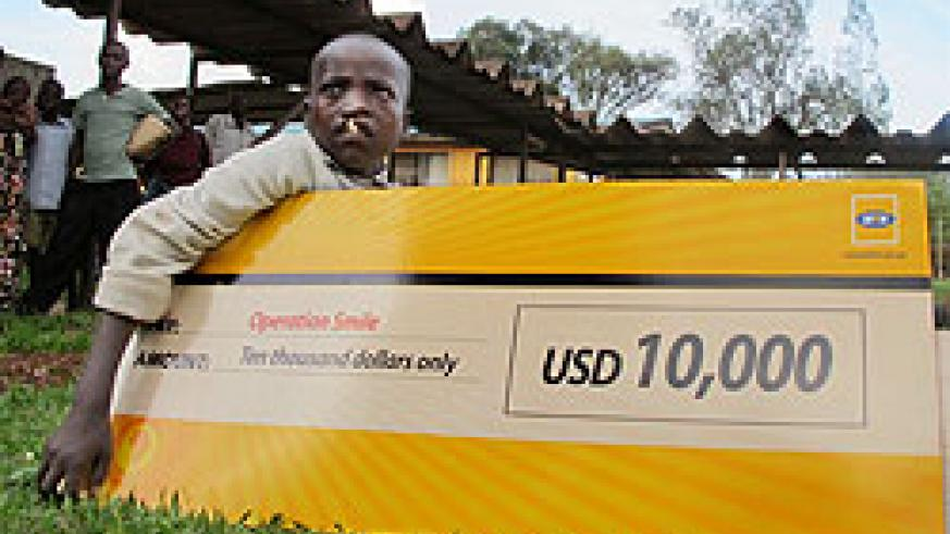 Alex Buhungiro, from Kirehe Distric,t holding a dummy cheque donanted to Operation Smile by MTN. (Photo T Kisambira)