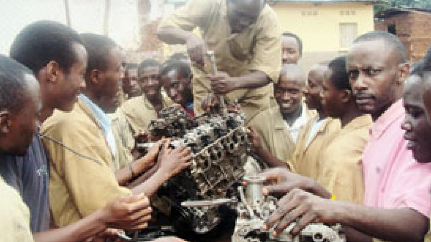 Students of CFR Kibungo helped by an instructor to assemble a motor engine. (Photo: S. Rwembeho)