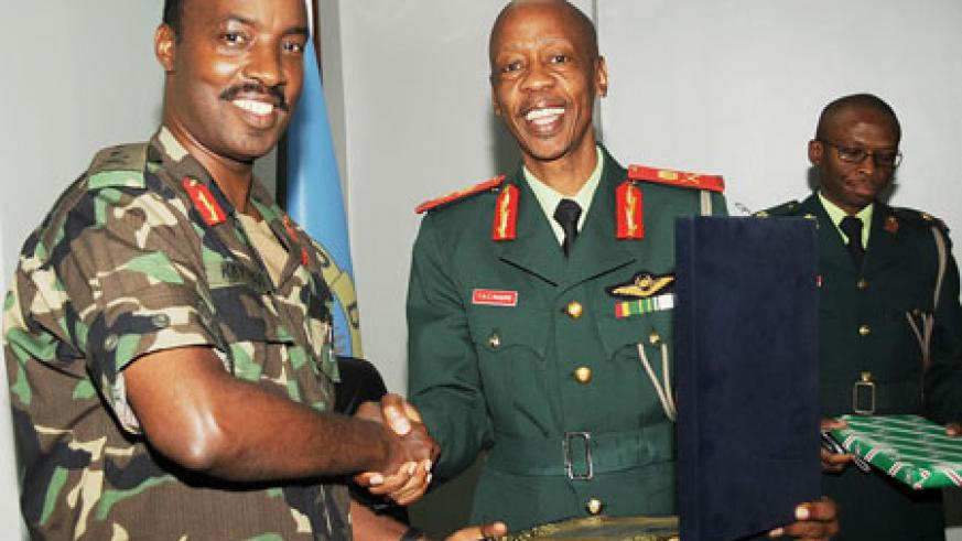 Chief of Defence Staff, Lt.Gen Charles Kayonga (L) ,exchanges gifts with his Botswana counterpart, Lt Gen.Tebogo Masire yesterday . (Photo J Mbanda)