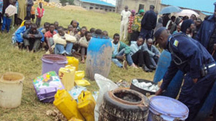 Residents watch some of the impounded local gin. (Photo: J.P Bucyensenge)