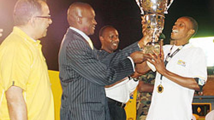 Former Sports Minister Joseph Habineza hands last year's MTN Peace Cup title to APR skipper Patrick Mafisango at Amahoro stadium. (File photo)