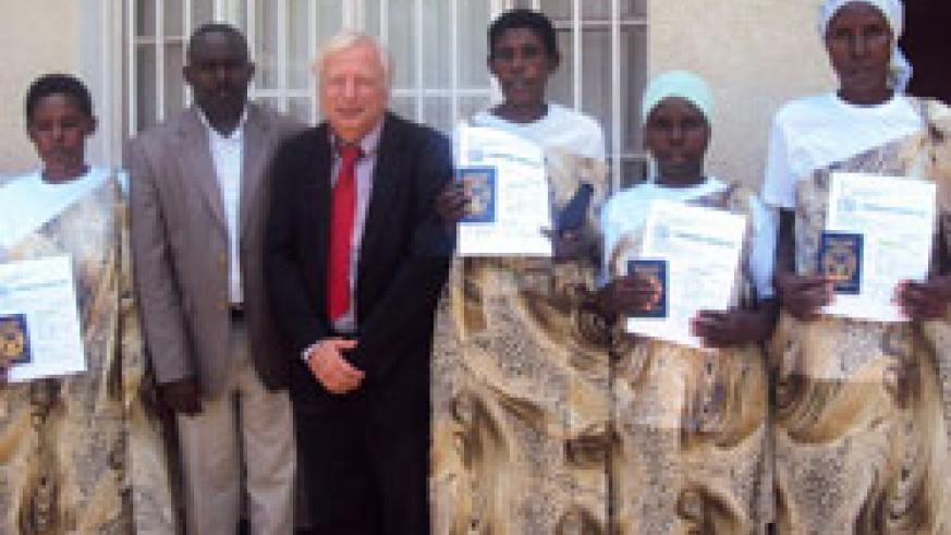 Mike Hughes and Mayor Louis Rwagaju  with the women after receiving their travel documents. (Photo S. Rwembeho)