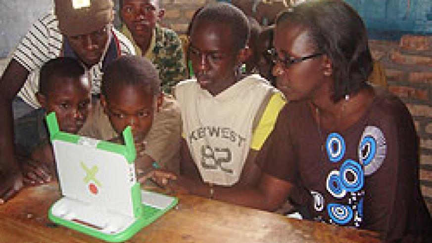 Caritas Kanizio, a Mineduc official gives ICT lessons to some of the Ruli Primary School pupils after the handover.Photo D.Sabiti)