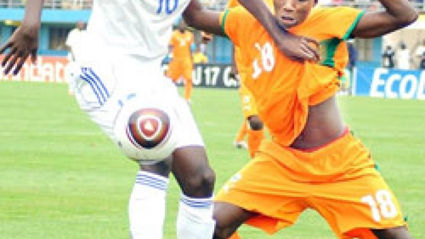 Junior Wasps' Andrew Buteera (L) shields the ball from an Ivory Coast player in the 2011 Caf U-17 championship in Kigali. (File photo)
