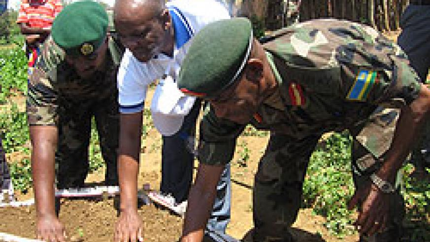 Brig.Gen Eric Murokore (R) and the Chief Operating Officer of BK, Lawson Naibo (c) together with another senior RDF officer launching the kitchen gardens (Photo: Dias Nyesiga)