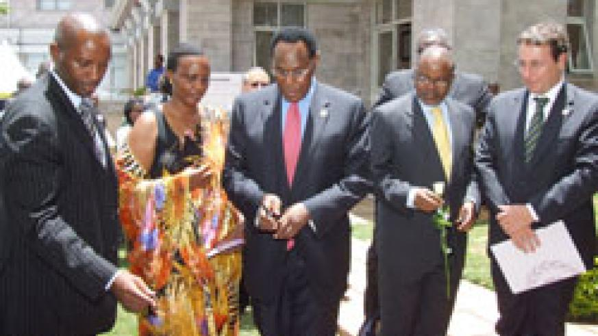 Kenya's acting Foreign Minister Prof George Saitoti (c) lights a candle of hope. High Commissioner William Kayonga is extreme left (Courtsey Photo)