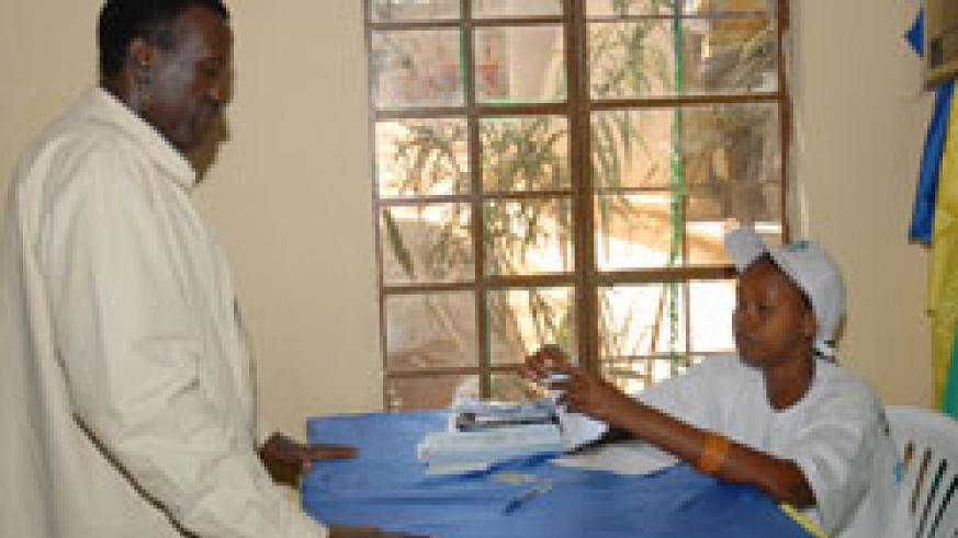 An electoral official attends to former Presidential aspirant Jean Damascene Ntawukuriryayo during the polls. Rwanda's use of volunteers has been lauded (File Photo)