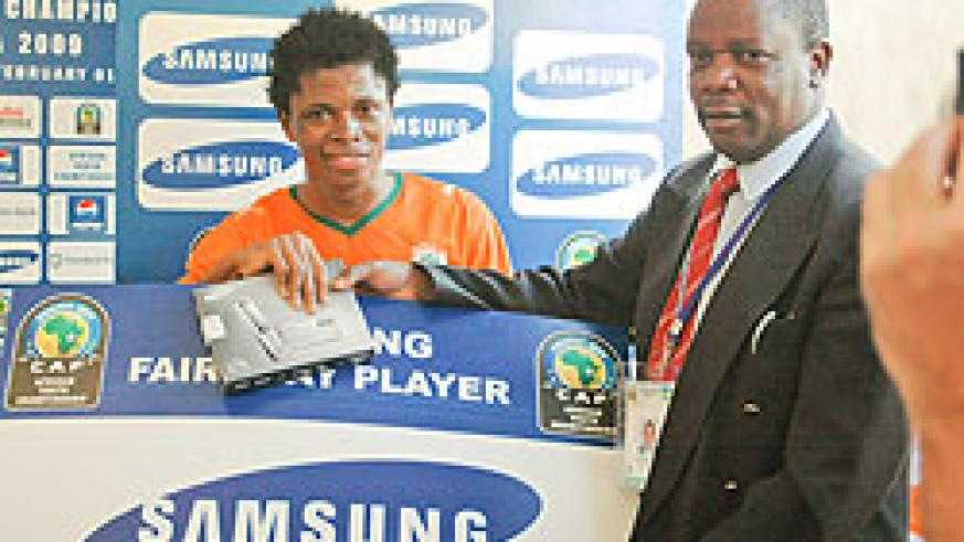 Nicholas Musonye (R) handing over the 'man of the match' award to an Ivory Coast player during the 2009 Caf U-20 championship. (File photo)