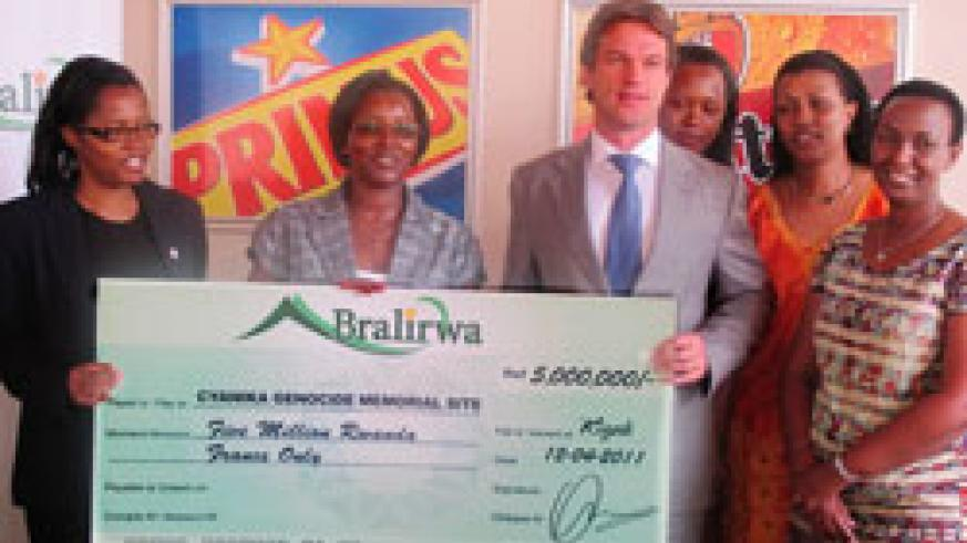 Sven Piederiet the managing Director of Bralirwa (C) hands over a dummy cheque to members of he Unity club (Photo T.Kisambira)