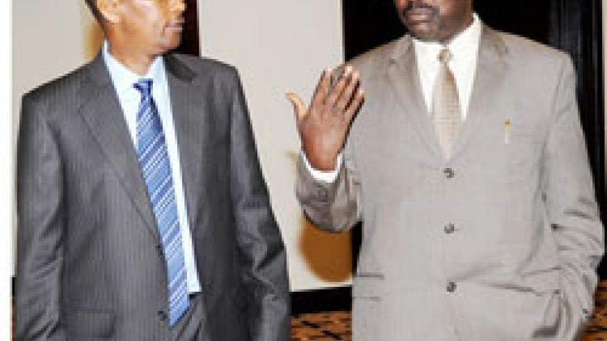 Central Bank Governor, Francois Kanimba (R)chats with the Finance Minister John Rwangombwa during the Monetary Policy statement presentation recently (File photo)