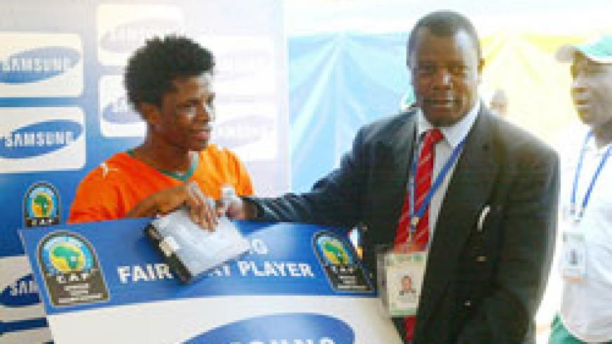 Cecafa SG Musonye (R) handing over the man of the match award to an Ivory Coast player during the 2009 U-20 Africa Championship. (File photo)