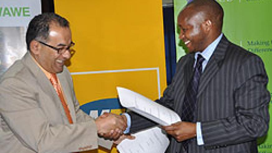 MTN's Chief Executive Officer, Khaled Mikkawi and Maurice K. Toroitich, the Managing Director of KCB Rwanda exchange documents after signing the deal