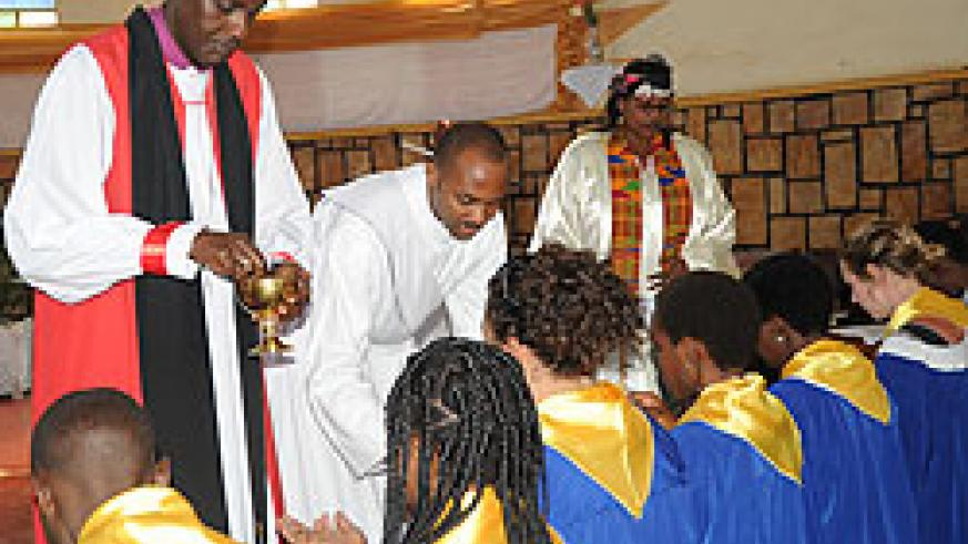 Kigali Diocese, Bishop Louis Muvunyi of St.Etienne (L) administers Holy communion to members of the church's choir during the Easter service, yesterday.(Photo J Mbanda).