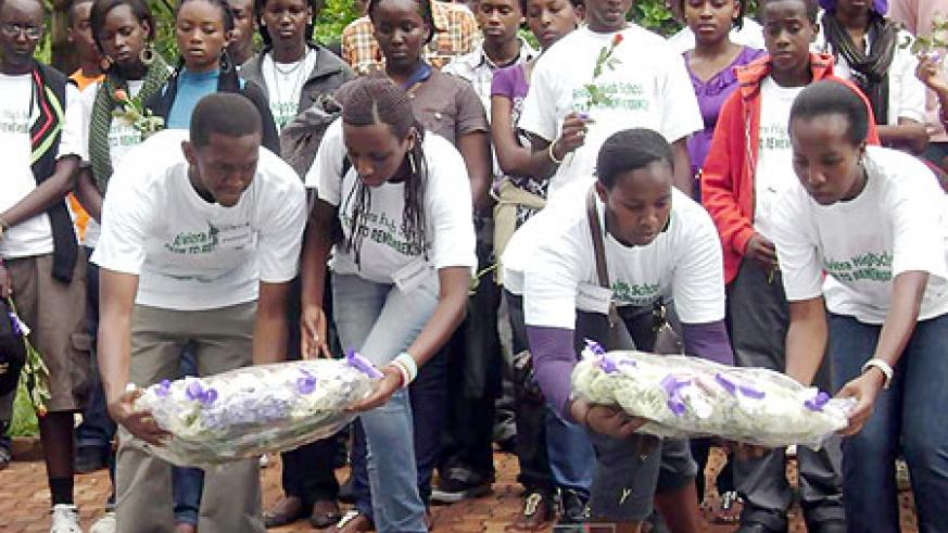 Student leaders and teacher (L) lay wreaths on the Mass graves