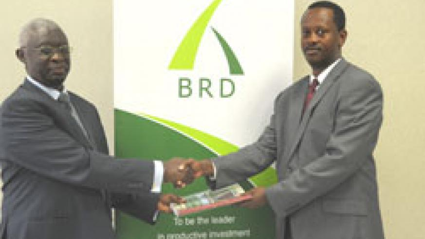 Former Managing Director of BHR Gervais Ntanganda exchanges documents with Jack Kayonga, the Managing Director of BRD (Photo T.Kisambira