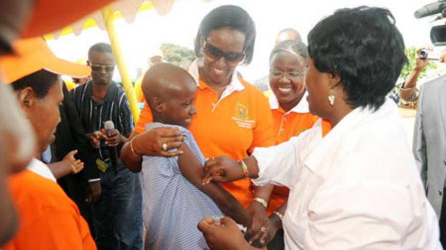 First Lady Jeannette Kagame comforts a girl after getting her vaccination from Dr Binagwaho. Minister Jeanne d'Arc Mujawamariya  looks on (Photo: J. Mbanda).