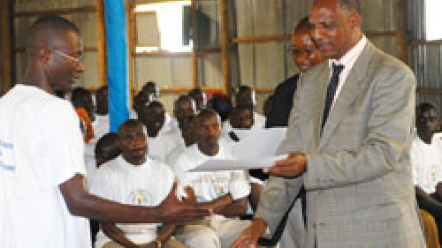 Demobilisation commission chairman, Jean Sayinzoga hands a certificate to ex-combatants after completing a course during a past event (File Photo)